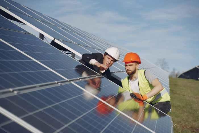 men discussing solar panels installation in field