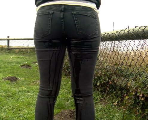 View from behind as Alisha pees in her tight, dark jeans.
