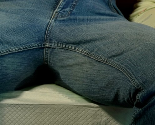 Close-up shot of Lola peeing in her jeans while Olivia fingers her.