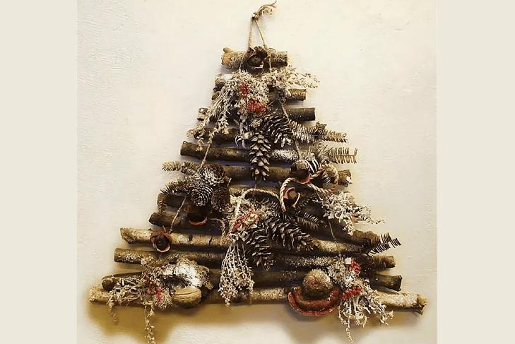 Árbol de Navidad original en la pared de palos y conos con sus propias manos.