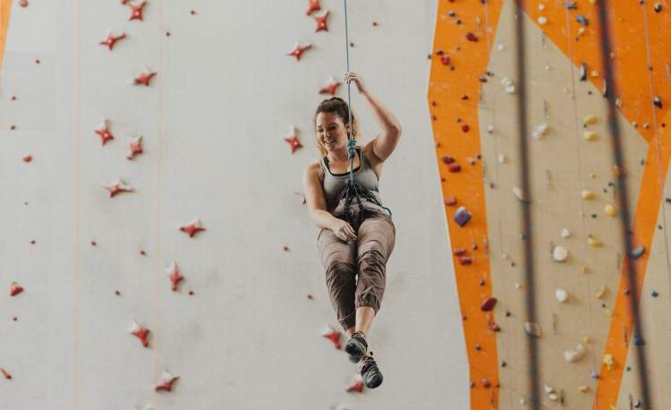 Woman suspended on rope by climbing wall. Metaphor for Research the five highs that lead to the best career choice.