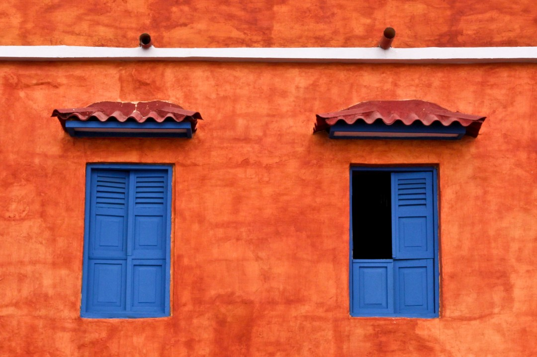Blue shutters on a coral color building in Cartagena