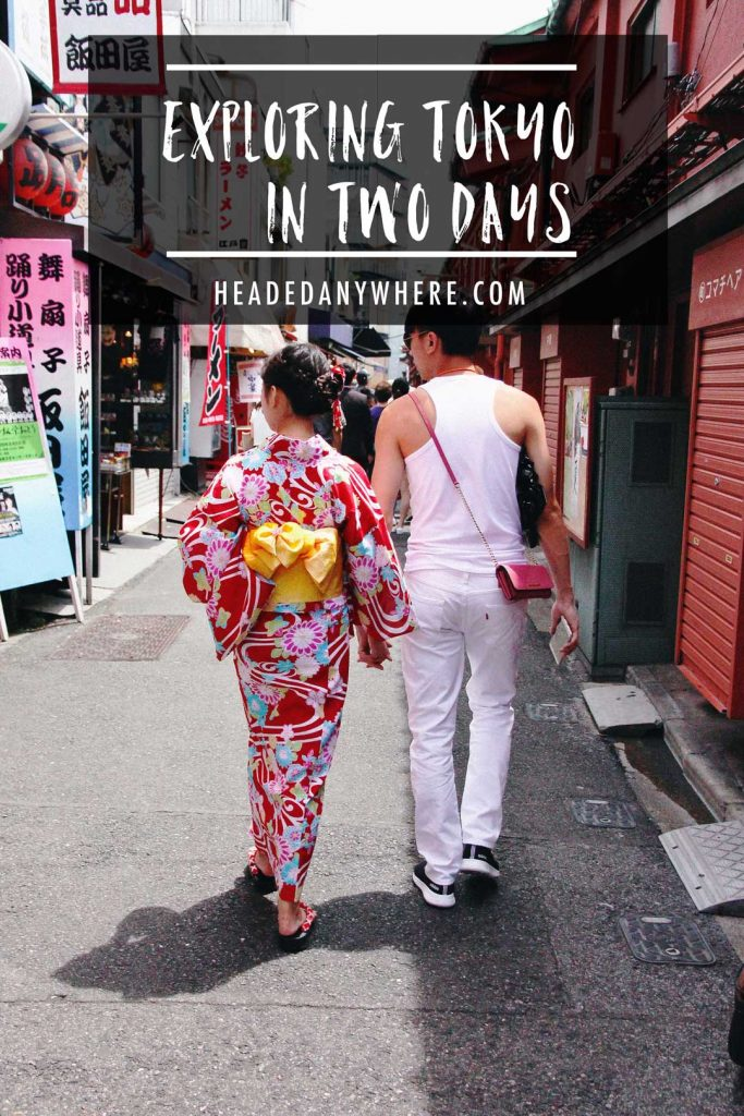 Woman in Kimono walking down street holding partner's hand.