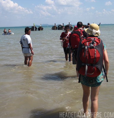 Daina walking through water to longtail boat in Railay with Osprey Bag