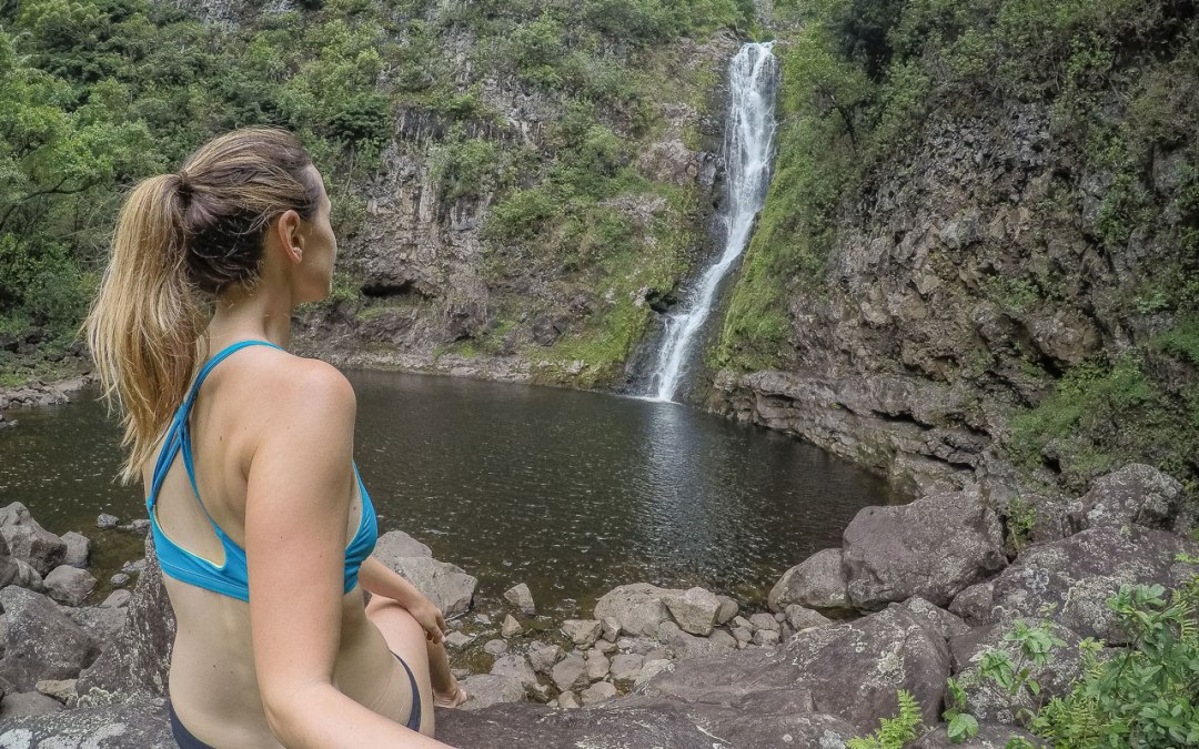 Woman sitting and looking at waterfall