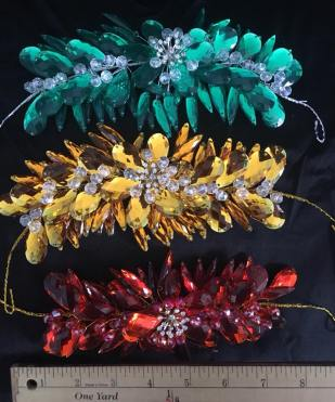 Three dimensional high quality resin pieces set on a bendable wire. Bobby pins will be needed to attach this headpiece. Available in gold, kelly green, and red. $25.00/each