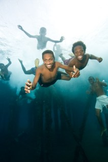No Model Release. Boys jumping and swimming under Jonny's Jetty, Kokopo/Rabaul, Papua New Guinea