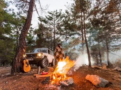 SUV camper with campfire in woods