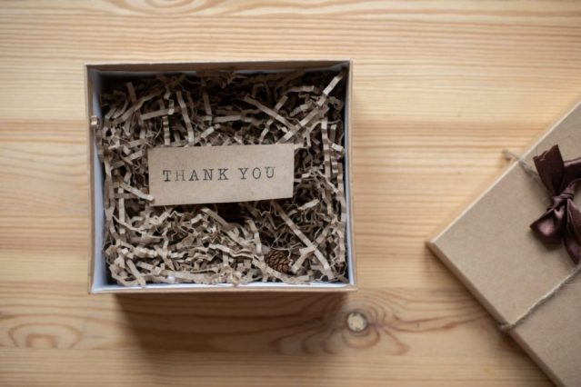 cardboard gift box with postcard on table