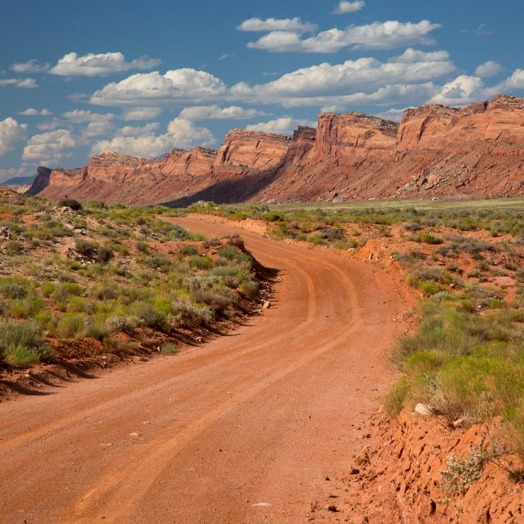 A red dirt road below rock bluffs in Bears Ears National Monument.