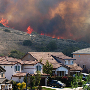 A wildfire burns over a ridge near a neighborhood.