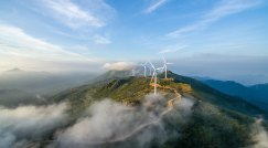Wind Turbines sit atop a hill with low clouds.