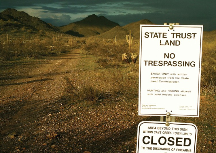 State Trust Land sign posted at road with rugged landscape. Cacti and sage are throughout the landscape.