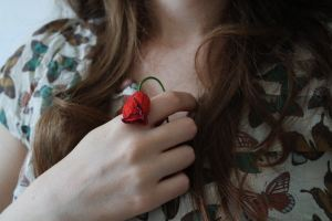 girl holding wilted flower to chest