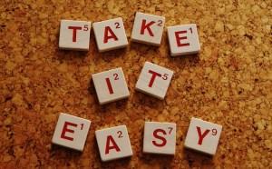 Take it easy written in red on white wooden scrabble tiles