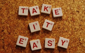 Take it easy written in red on white wooden scrabble tiles