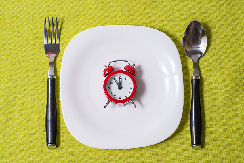 small clock on a white plate on grey tablecloth with fork and spoon on either side of plate