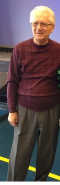 Photo of Ossie, a Holocaust survivor, dressed in gray slacks with a maroon sweater.