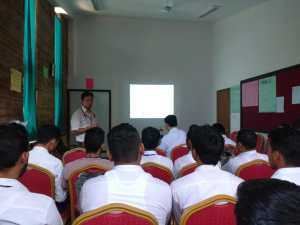 People in white coats face away from the camera towards a presentation