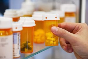 A woman reaching for a prescription bottle in a medicine cabinet