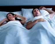 Man snoring with woman awake