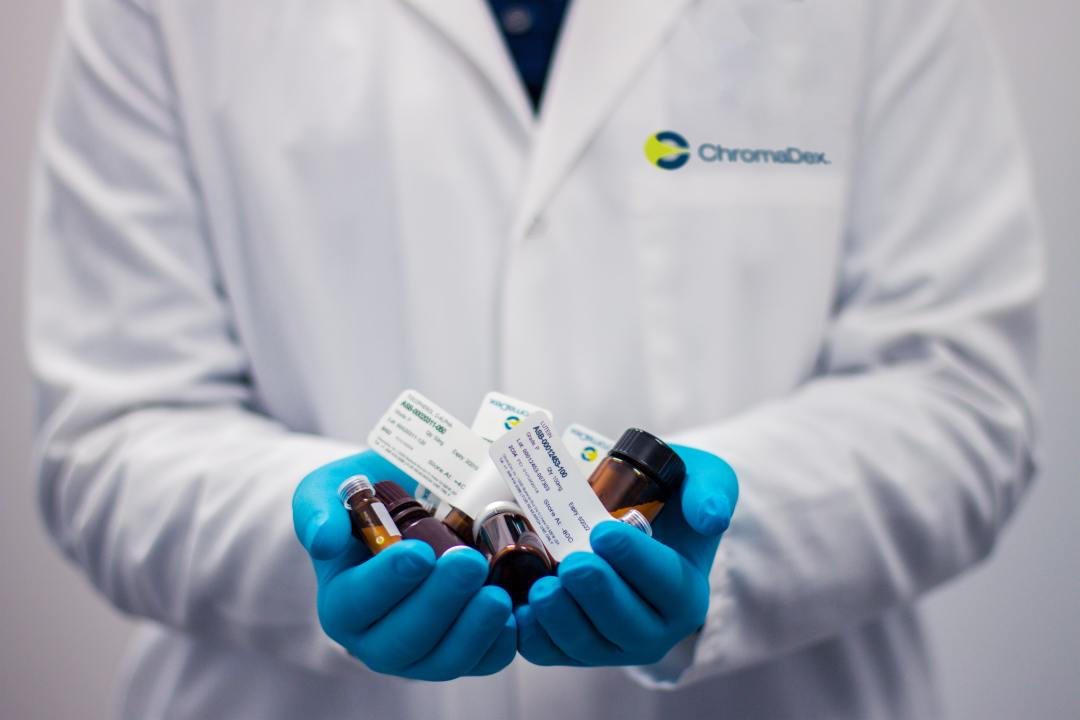 A doctor working in healthcare manufacturing and research holding out a number of pills and healthcare products.