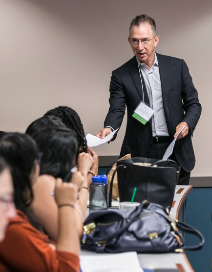 David Ansell, Rush University Medical Center, hands out information prior to a panel discussion as DePaul University and their Center for Community Health Equity host the annual Health Disparities and Social Justice Conference Friday, Aug. 12, 2016, on the Loop campus. The conference focused on social justice in the context of public health in Chicago. (DePaul University/Jamie Moncrief)