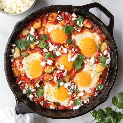 Best ever healthy shakshuka recipe in cast iron skillet with lots of fresh vegetables and crumbled feta.