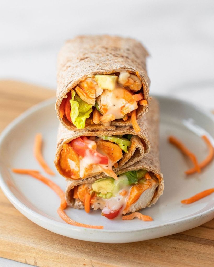 Close up image of buffalo chicken caesar wraps stacked on top of each other. Super easy healthy lunch recipe. Loaded with organic chicken, buffalo sauce, avocado, fresh vegetables, and wrapped in a low calorie whole wheat wrap.