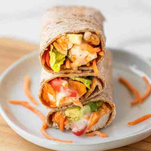 Super easy and delicious healthy buffalo chicken caesar wraps. Ready in 15 minutes, this easy on-the-go lunch or dinner recipe is perfect for meal prep, fitness lovers, and families. They are loaded with chicken, avocado, buffalo sauce, whole wheat wraps, Caesar dressing, and lots of fresh veggies! Made gluten free, dairy free, low calorie, paleo, high protein, and low fat.