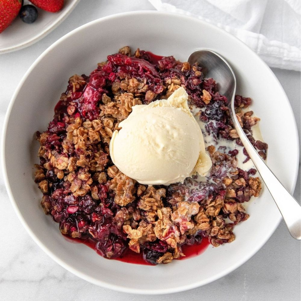 Best healthy mixed berry orange crisp made with simple ingredients and topped with a delicious oat crumble and vanilla ice cream. This easy and healthy dessert recipe is vegan, gluten free, and dairy free! This is a must-try dish that you're guaranteed to love! Recipe by Healthful Blondie.