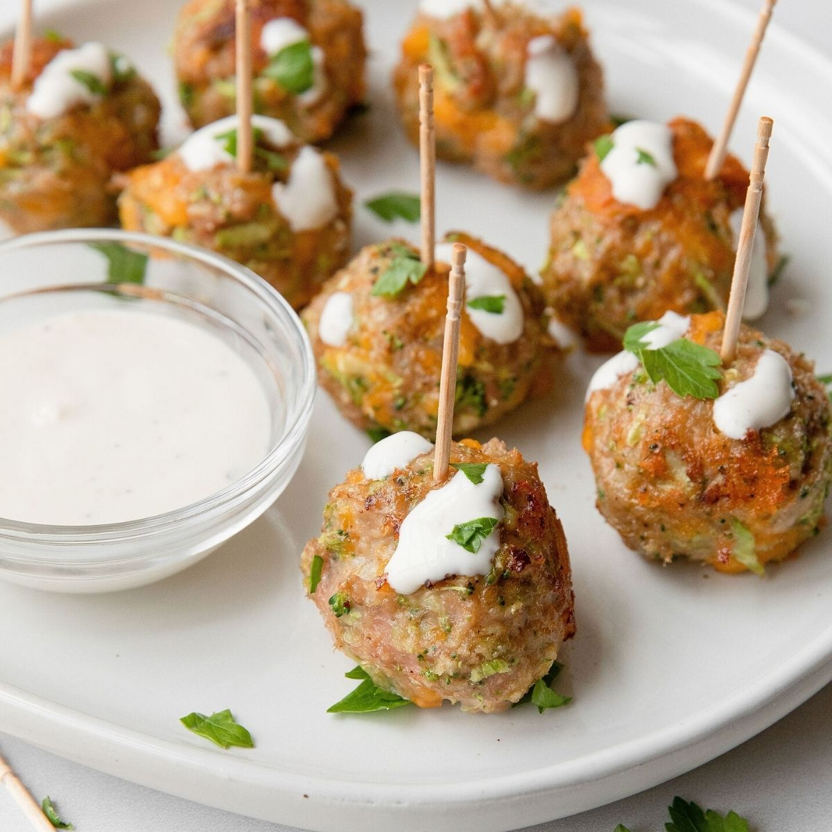 Incredibly easy, juicy, and delicious healthy broccoli cheddar turkey meatball poppers drizzles with caesar dressing or ranch dressing. Simple meatball skewer recipe.