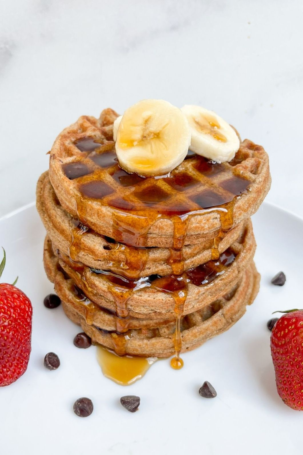 Stack of vegan flourless banana oatmeal waffles with maple syrup