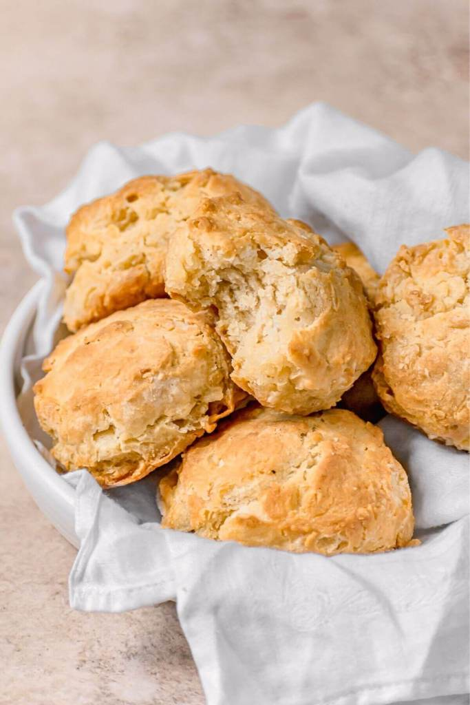 bite shot of Southern buttermilk biscuits made with almond milk in a basket