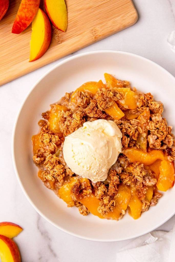 peach crumble in a bowl with ice cream