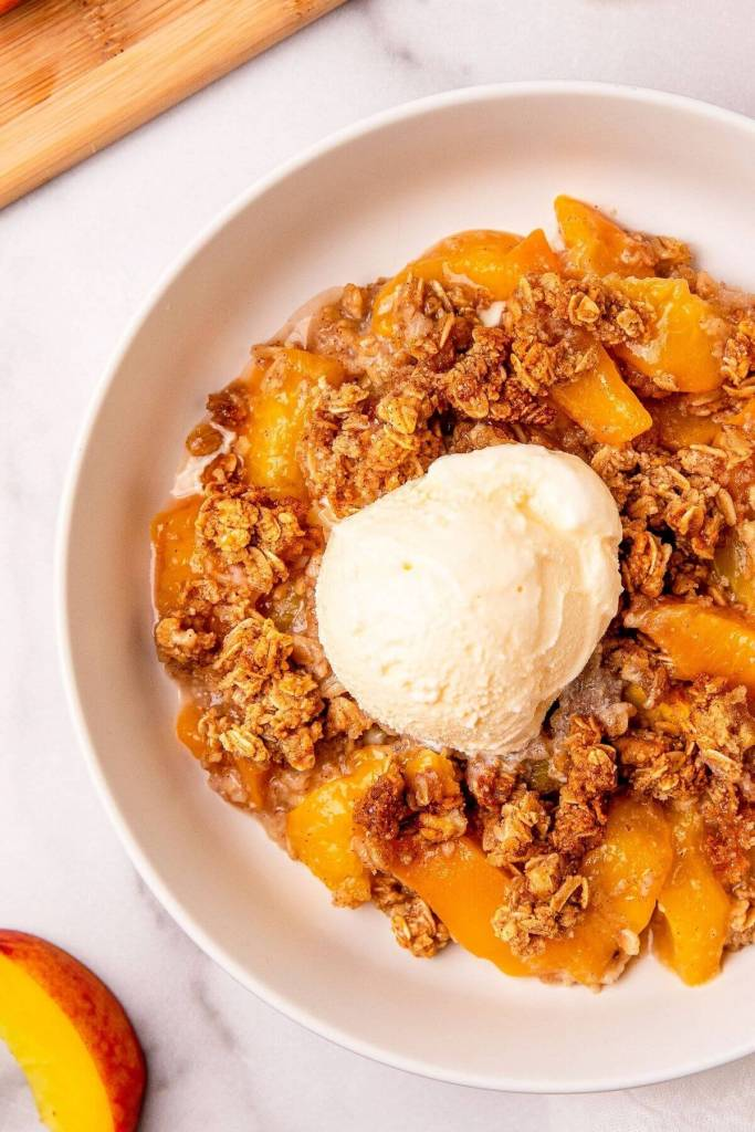 close up of healthy peach crisp with streusel topping