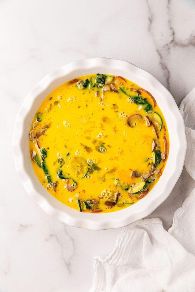 whisked eggs and veggies in pie dish to make crustless quiche