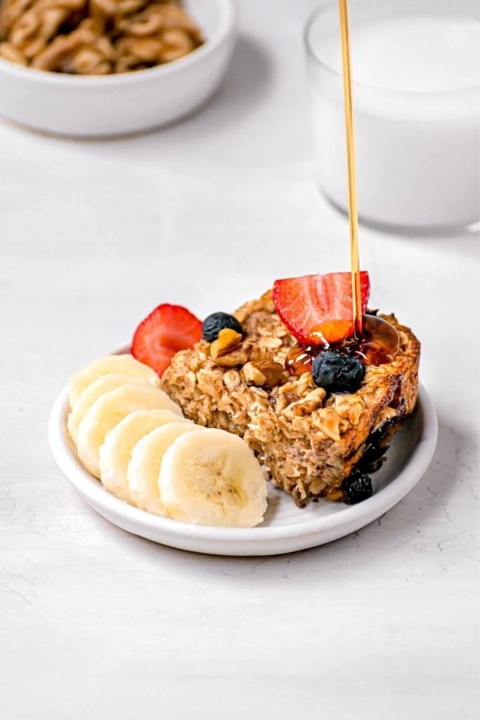 square of vegan baked oats with maple syrup pouring on top