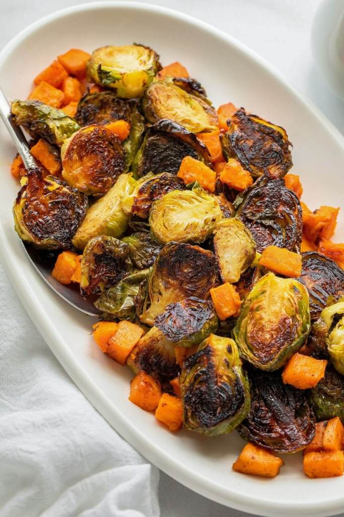 close up of crispy roasted maple sweet potato and brussels