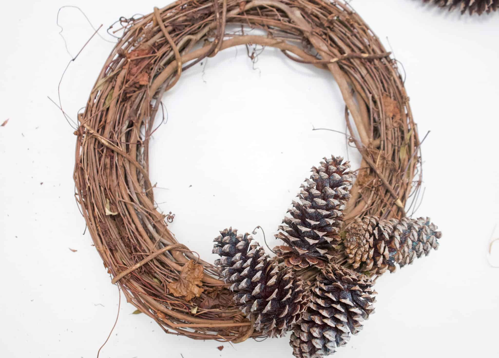Are you looking for a lovely, neutral wreath that will last you through the winter season without breaking the bank? Check out this tutorial on how to make your own holiday pinecone wreath!