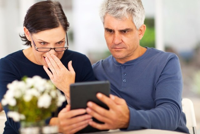 middle aged couple reading shocking news on tablet computer