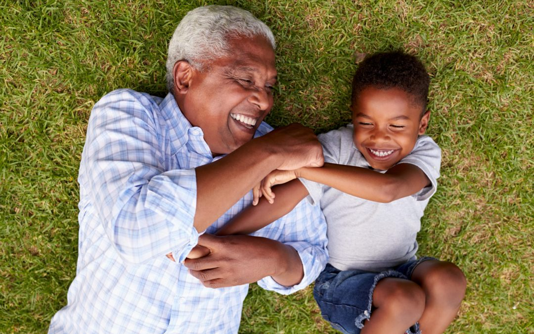 A man lying in the grass laughing with his grandson.