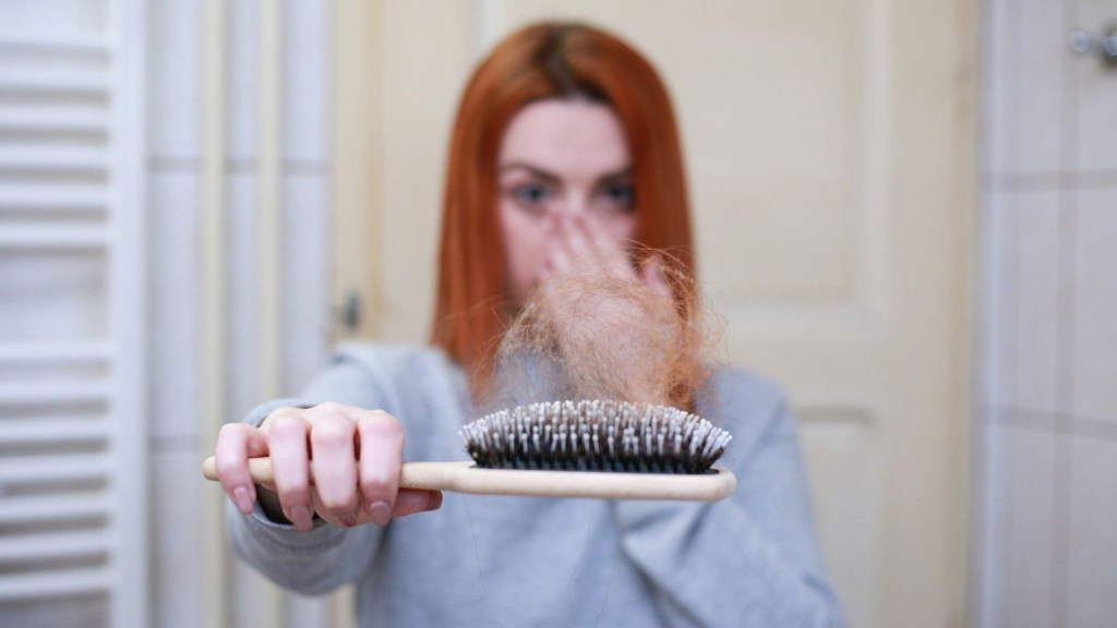 Girl with hair loss on a hairbrush
