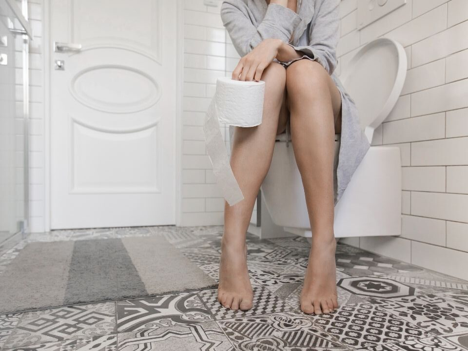 Legs of a person sitting on a toilet