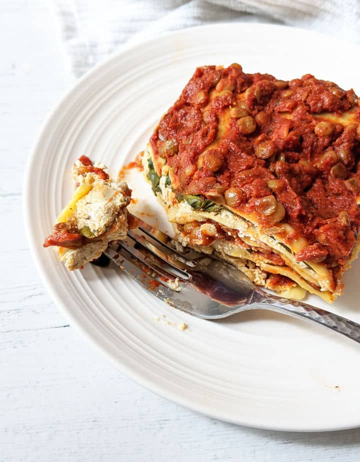 slice of lasagna on a plate with a fork
