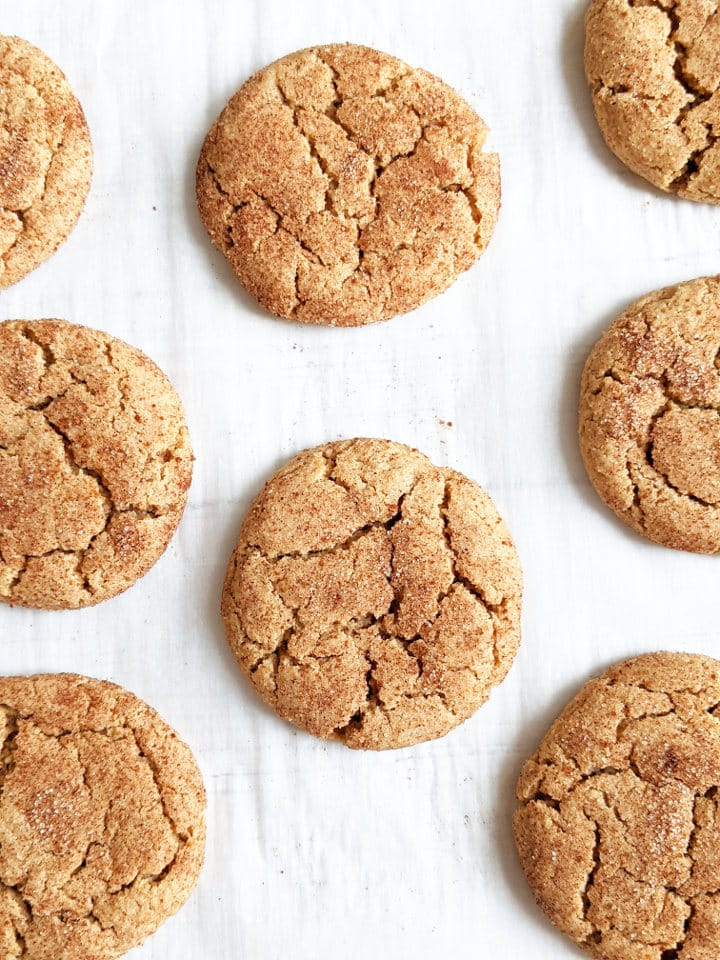 baked snickerdoodles laying on parchment paper