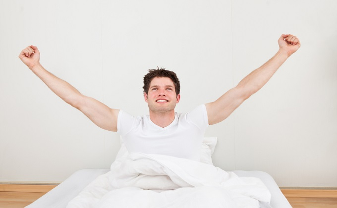 Man With Arm Raised On Bed