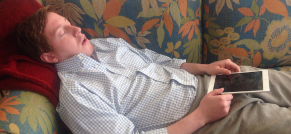 Young man sleeping on couch with tablet 600x277