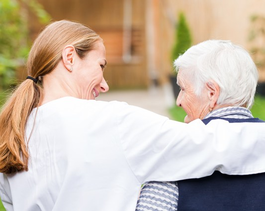 Carer with her arm around an older lady