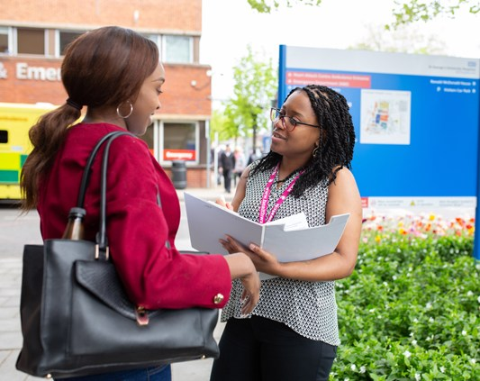a woman answers questions from another woman with a clipboard outside a hospital